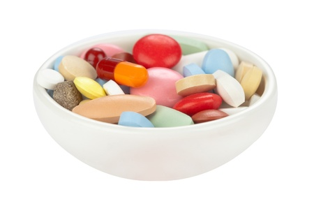Colored pills in white bowl Stock Photo
