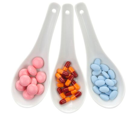antibiotic pills: Three ceramic spoons with colorful pills Stock Photo