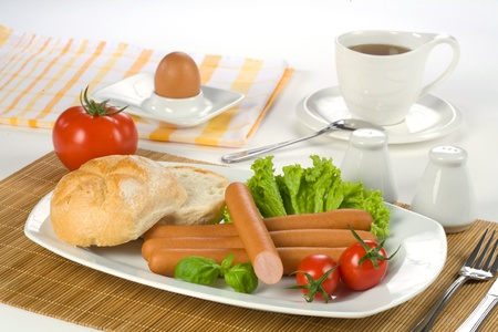 Breakfast sausages, tomato, egg, and cup of tea Stock Photo