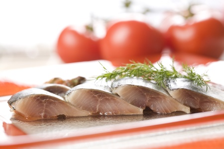 Four herring slices with tomato background