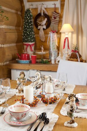 christmas table set with candles, sculptures and christmas tree photo