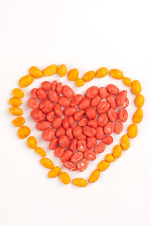 dragees: Red heart and yellow contour made of dragees of peanuts
