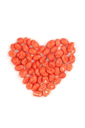 Red heart made of dragees of peanuts, isolated photo