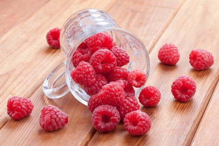 fresh raspberries spilling from a cup Stock Photo