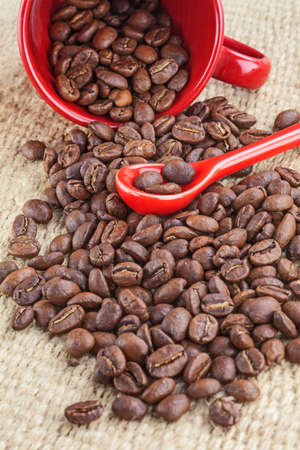 Spilled coffee seeds and red cup and spoon photo