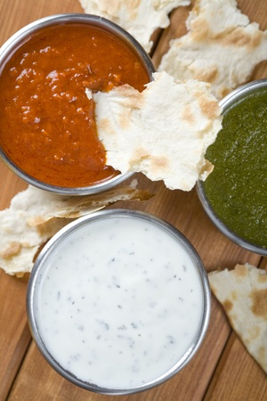 Mint chutney, mint yogurt and spicy pepper dip. White, green and red.  photo