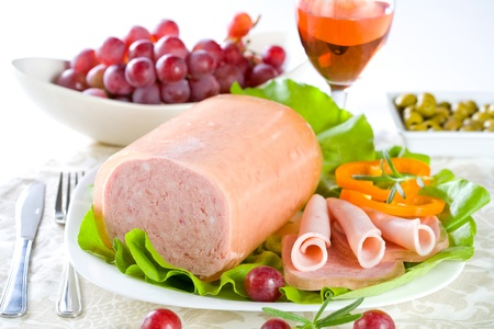 Luncheon meat, salad, olives and grapes  photo