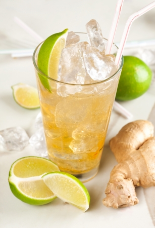 alcoholic beverages: Yellow drink with lime, ginger and ice Stock Photo