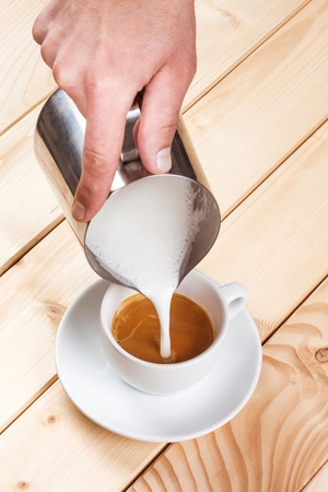 Pouring frothed milk into a cup of coffee, pattern creation Stock Photo - 22114741