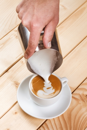 Pouring frothed milk into a cup of coffee, pattern creation Stock Photo - 22114742
