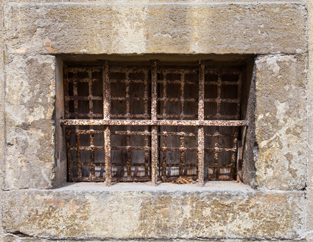 Horizontal old window with rusty bars photo