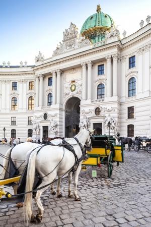 hofburg: Vienna, Austria - August 30, 2013; Main entrance to Hofburg palace  Horse-drawn carts waiting for tourists at the main gate to Hofburg Palace in Vienna