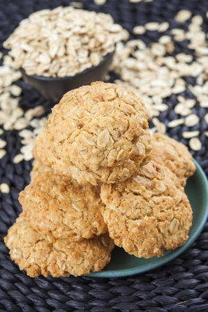 oatmeal cookies: Oatmeal cookies on green plate, scattered oat flakes Stock Photo