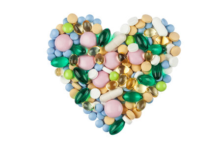 Heart shape made of color pills and capsules, isolated on white photo