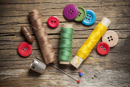 Set of colored sewing buttons and bobbin threads on wooden background Banque d'images