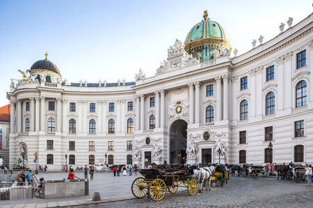 Vienna, Austria - August 30, 2013; Main entrance to Hofburg palace Horse-drawn carts waiting for tourists at the main gate to Hofburg Palace  Editorial