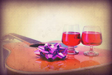 Grunge vintage Celebrate the day in the past with Folk Guitar and Two wine glasses photo
