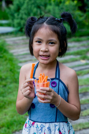 healthy snack: Little kid with a yummy sweet carrot