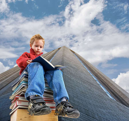 a boy sitting on a stack of books by a building Stock Photo