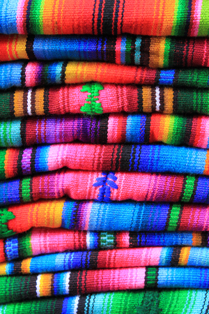 fabric textures: A stack of traditional colourful Guatemalan woven fabrics sold in a market in Chichicastanengo Guatemala