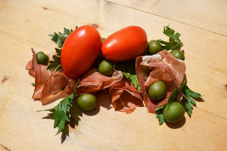Speck, tomatoes, olives and parsley on wood photo