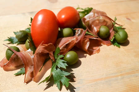 Speck, tomatoes, parsley and olives on wood photo