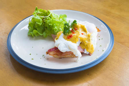 uk cuisine: Eggs Benedict- toasted English muffins, Bacon, poached eggs, and delicious buttery hollandaise sauce Stock Photo
