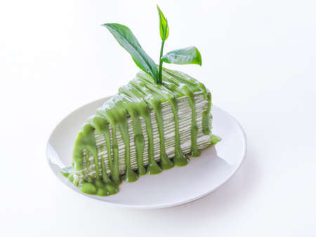 Green tea crepe cake with green tea sauce is on white plate