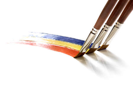 three brushes painting colors Standard-Bild