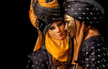 venetian couple in yellow costume isolated on black background photo
