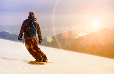 sun track: Man snowboarding Stock Photo