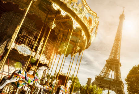 vintage carousel close to Eiffel Tower, Paris with sun flare effect