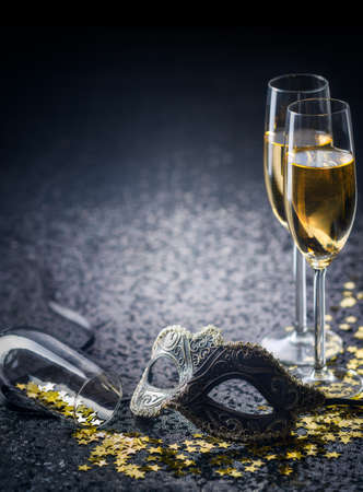 mask and champagne with star shaped confetties Standard-Bild