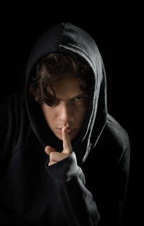hooded teen has a secret Standard-Bild