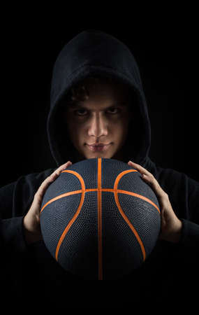 insolent hooded boy holding basketball