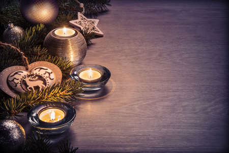 Christmas decoration and candle on wooden board