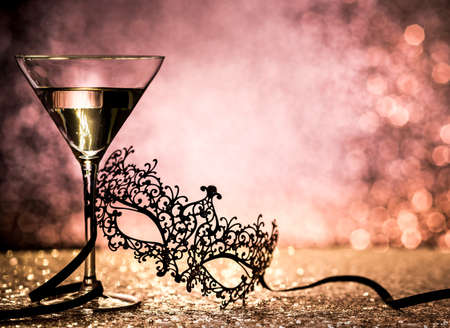 Carnival mask and cocktail with copy space on glittering background