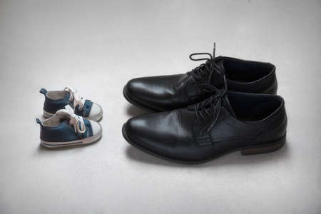 Father with Child Metaphor, baby and adult shoes Standard-Bild