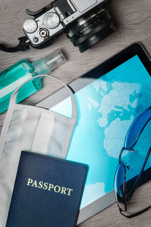 safe traveling during a pandemic crisis, passport with mask, map and other accessories