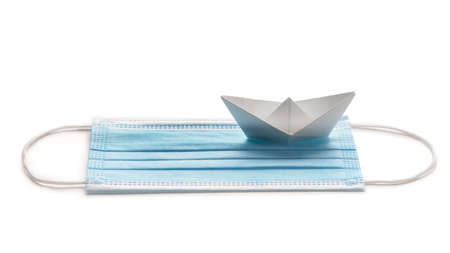 Sailing during pandemic crisis. Surgical mask with white paper ship on white background. Standard-Bild
