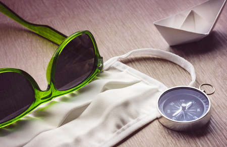 Safe Travel, mask and compass with green sunglasses