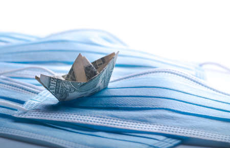 Dollar tosses on the waves. Financial problems concept, banknote origami-ship with surgical masks.