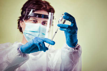 Vaccination, doctor in protective clothes with syringe and ampule Standard-Bild