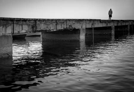 Sorrow. Silhouette of a lonely man on a pier, black and white image.
