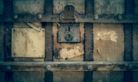 front of an old shabby chest with a padlock and a blank sticker