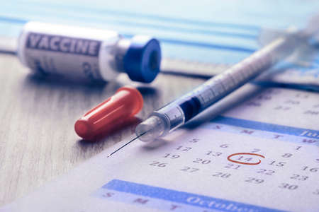 vaccination day, close-up of a syringe and vaccine with calendar on a table Standard-Bild