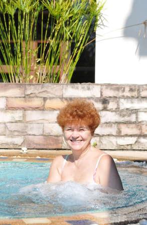 Happy beautiful senior woman in jacuzzi looking at camera