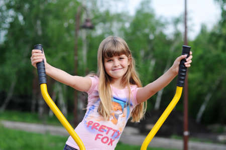 training device: Happy girl doing fitness portrait. She is eight years old and looking at camera. Stock Photo