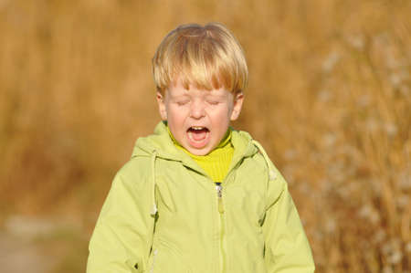 oppressed: Crying blond boy portrait in green jacket outdoor Stock Photo