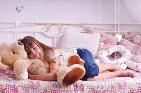 Sleeping girl with big plush bear lying on the bed